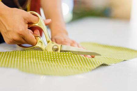 tijeras: Cerca de las manos de la mujer a medida irreconocible corte de tejidos de puntos verdes con unas tijeras
