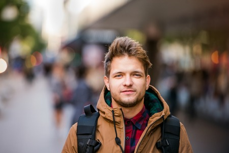 winter jacket: Close up of young hipster man in brown winter jacket walking in the streets of London