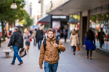 winter jacket: Young hipster man in brown winter jacket walking in the streets of London