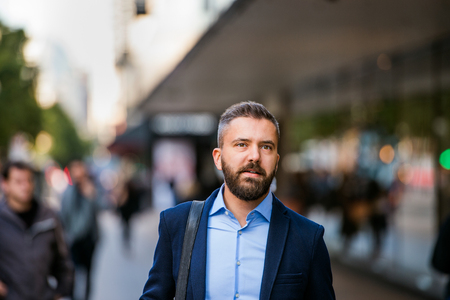 busy beard: Hipster manager in blue shirt and jacket walking in the street of London
