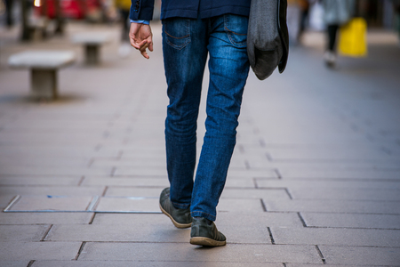 back view: Legs of unrecognizable manager walking in the street of London, back view
