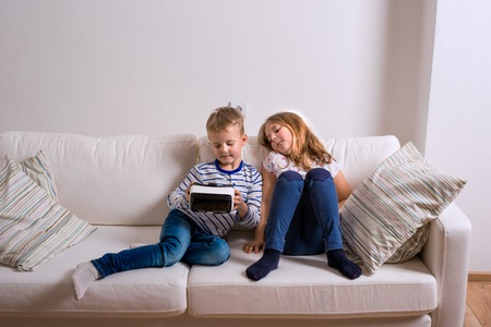 digital device: Little girl and boy in striped t-shirt wearing virtual reality goggles. Studio shot, white couch Stock Photo