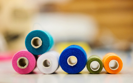 laid: Composition with spool of colorful tailor threads laid on table Stock Photo