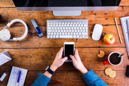 hand lay: Business person working at office desk. Smart watch on hand, holding a smart phone. Coffee cup, notepad and various office supplies around the workplace. Flat lay. Stock Photo