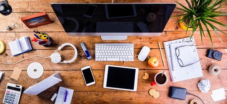 Biurko z różnymi gadżetami i artykułami biurowymi. Komputer, inteligentny telefon, tablet i materiały piśmienne w całym miejscu pracy. Płaskie leże.