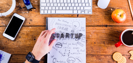 hand lay: Business person at office desk working. Smart watch on hand and smart phone on the table. Start up sign made of cookie cutters. Coffee cup, notepad and various office supplies around the workplace. Flat lay.