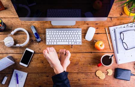D'affari che lavora nel suo ufficio con i piedi sulla scrivania. Smart phone e vari articoli per ufficio in tutto il posto di lavoro. disteso.