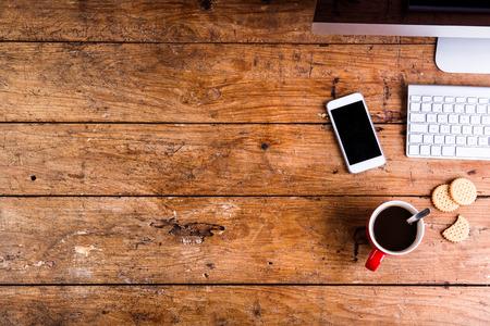 galletas: Escritorio con aparatos y equipos de oficina. El teclado de ordenador, teléfono inteligente, café y galletas todo el lugar de trabajo. aplanada. Espacio de la copia.
