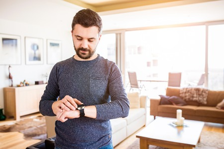 device: Casual hipster man working from home using smart watch, standing in living room