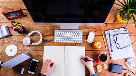 person writing: Business person working at office desk, writing into a notebook. Smart phone on the table. Copy space. Flat lay.