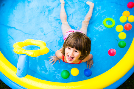 personas banandose: Niña linda que se divierte en azul jardín piscina. Soleado día de verano en el patio trasero Foto de archivo