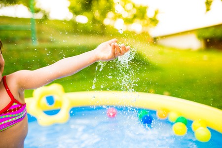 water garden: Hand of unrecognizable girl having fun in yellow garden swimming pool. Sunny summer day at the backyard
