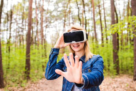outstretching: Blond woman wearing virtual reality goggles outside in green forest, spring nature Stock Photo