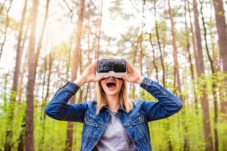 Blond woman wearing virtual reality goggles outside in green forest, spring nature Stock Photo