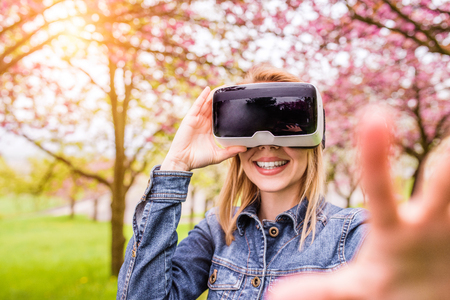 outstretching: Blond woman wearing virtual reality goggles outside in spring nature