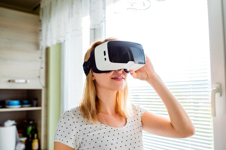 Blond woman wearing virtual reality goggles standing in a kitchen