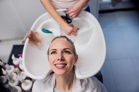 Onherkenbaar professionele kapper wassen van het haar om haar mooie cliënt. Jonge vrouw in een kapsalon