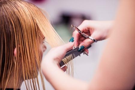 認識できないプロの美容師が女性客に新しいヘアカットを与える彼女のクライアントの髪をカットの手。 写真素材