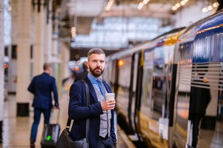 busy beard: Hipster businessman holding a disposable coffee cup at the train station platform