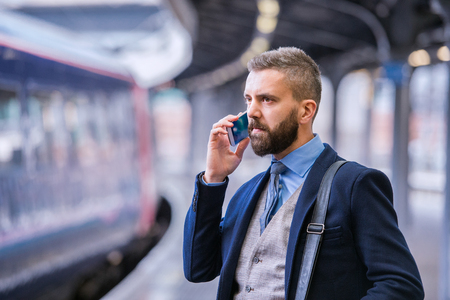 speaking tube: Hipster businessman with smartphone, making a phone call, walking at the train station platform