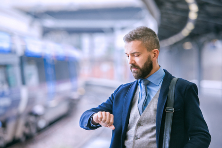 smiling businessman: Close up of hipster businessman waiting at the train station platform, looking at watch on hand