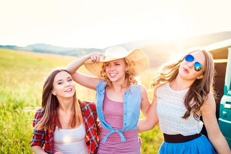 roadtrip: Three teenage hipster girls on a roadtrip. Young friends outside on a summer day