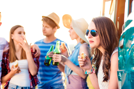 roadtrip: Group of teenage hipsters on a roadtrip, drinking beer, eating. Young friends outside on a summer day. Stock Photo