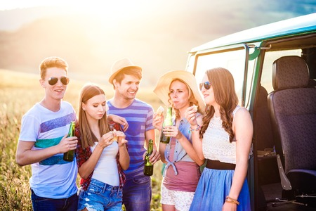 young group: Group of teenage hipsters on a roadtrip, drinking beer, eating. Young friends outside on a summer day. Stock Photo
