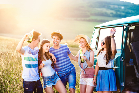 roadtrip: Group of teenage hipsters on a roadtrip, drinking beer. Young friends outside on a summer day. Stock Photo