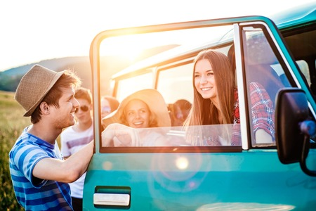 fun day: Group of teenage hipsters on a roadtrip having fun, standing at the campervan. Young friends outside on a summer day. Stock Photo