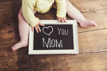 Composition du jour des mères. Bébé non reconnaissable en onesie jaune tenant un panneau de craie dans un cadre. Studio tiré sur un fond en bois. Banque d'images