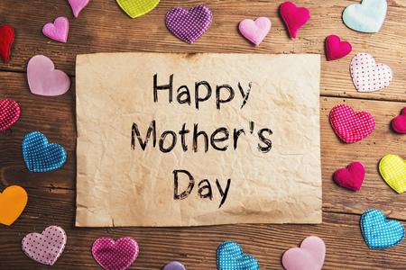 Glückliche Mütter Tag Zeichen. Mütter Tag Zusammensetzung. Bunte Stoffherzen. Studioaufnahme auf Holzuntergrund. Standard-Bild - 55746002