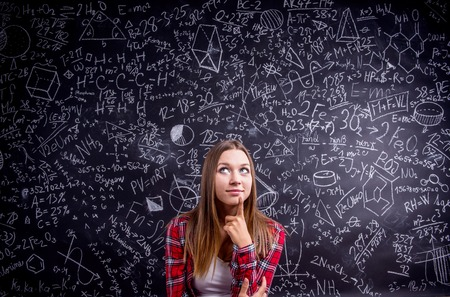wise woman: Beautiful student in red checked shirt against big blackboard with mathematical symbols and formulas. Studio shot on black background. Stock Photo