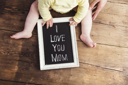 day: Composición del día de madres. bebé irreconocible en tela de color amarillo con un cartel de tiza en marco. Estudio tirado en el fondo de madera.