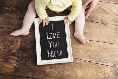 Mothers day composition. Unrecognizable baby in yellow cloth holding a chalk sign in picture frame. Studio shot on wooden background.
