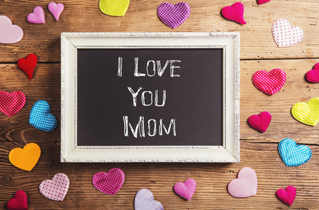 i love you sign: Mothers day composition. I love you sign in picture frame. Colorful fabric hearts. Studio shot on wooden background.
