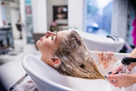 Onherkenbaar professionele kapper wassen van het haar om haar mooie cliënt. Jonge vrouw in een kapsalon Stockfoto
