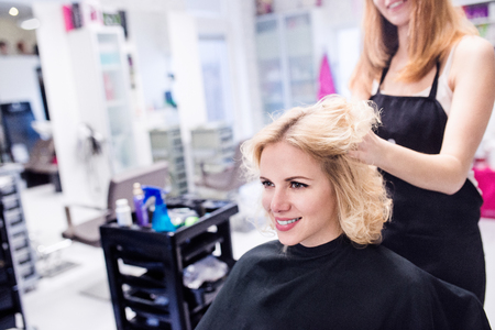 Professional hairdresser making new haircut to her beautiful blond client. Stock Photo