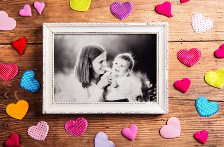 old photo: Mothers day composition.  Photo of mother with her son in picture frame. Colorful fabric hearts. Studio shot on wooden background.