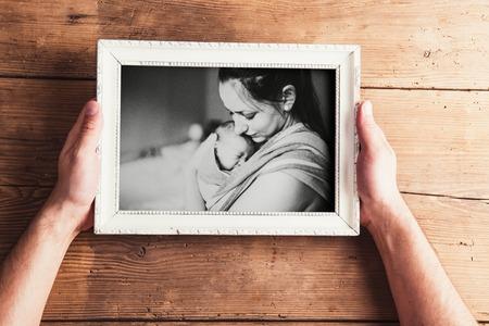 Moederdag samenstelling. Handen van onherkenbare man die een foto van moeder en baby dochter houdt. Studio schot op houten achtergrond. Stockfoto