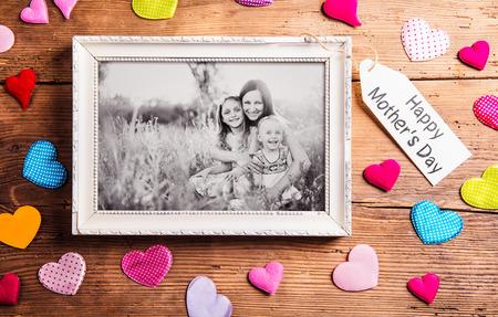 madre: Composición del día de madres. Foto de la madre con sus hijas en el marco de imagen. corazones de tela de colores. Estudio tirado en el fondo de madera.