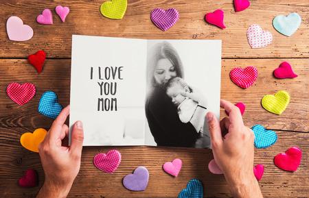 Moeders dag samenstelling. Handen van onherkenbare man met zwart-wit foto van de moeder met haar baby dochter. Kleurrijke stof harten. Studio opname op houten achtergrond. Stockfoto