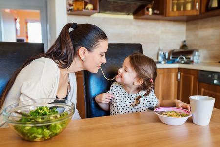 joven madre con su pequeña hija linda en la cocina, comiendo espaguetis juntos