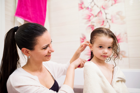 combing hair: Beautiful young mother combing hair of her little daughter after taking bath Stock Photo