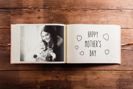 albums: Mothers day composition. Photo album, black-and-white picture. Studio shot on wooden background.