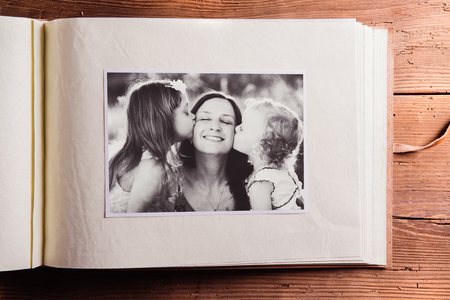 album greetings: Mothers day composition. Photo album, black-and-white picture. Studio shot on wooden background.