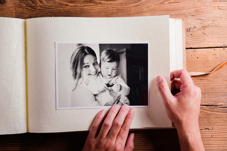 Moeders dag samenstelling. Handen van onherkenbare man die een foto album, zwart-wit beeld. Studio opname op houten achtergrond.