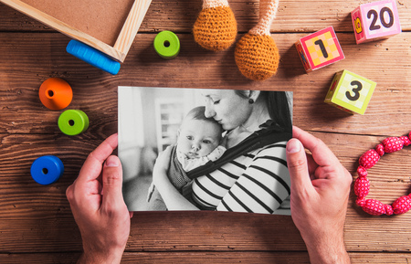 mother: Mothers day composition. Unrecognizable man holding black-and-white picture. Various toys. Studio shot on wooden background.