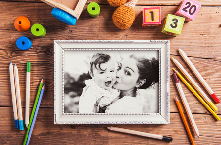 blackandwhite: Mothers day composition. Black-and-white photo in picture frame. Various toys. Studio shot on wooden background.