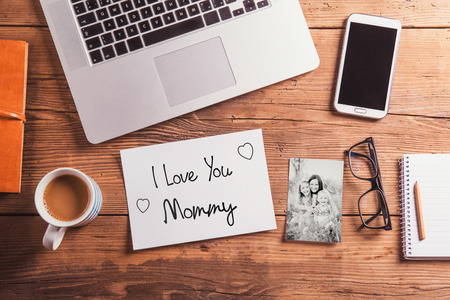 Mothers day composition. I love you Mommy note and black-and-white photo. Office desk. Studio shot on wooden background.